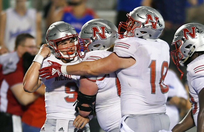 Nicholls State quarterback Chase Fourcade (9) is mobbed by teammates after scoring the winning touchdown in overtime against Kansas during an NCAA college football game in Lawrence, Kan., Saturday, Sept. 1, 2018. (AP Photo/Reed Hoffmann)