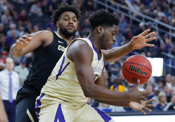 Colorado's Evan Battey, left, and Washington's Noah Dickerson vie for a rebound during the second half of an NCAA college basketball game in the semifinals of the Pac-12 men's tournament Friday, March 15, 2019, in Las Vegas. (AP Photo/John Locher)