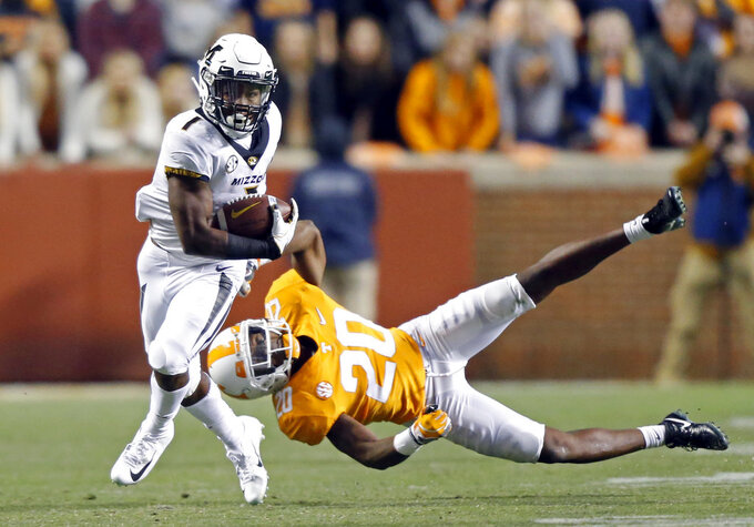 Missouri running back Tyler Badie (1) escapes from Tennessee defensive back Bryce Thompson (20) in the second half of an NCAA college football game Saturday, Nov. 17, 2018, in Knoxville, Tenn. (AP Photo/Wade Payne)