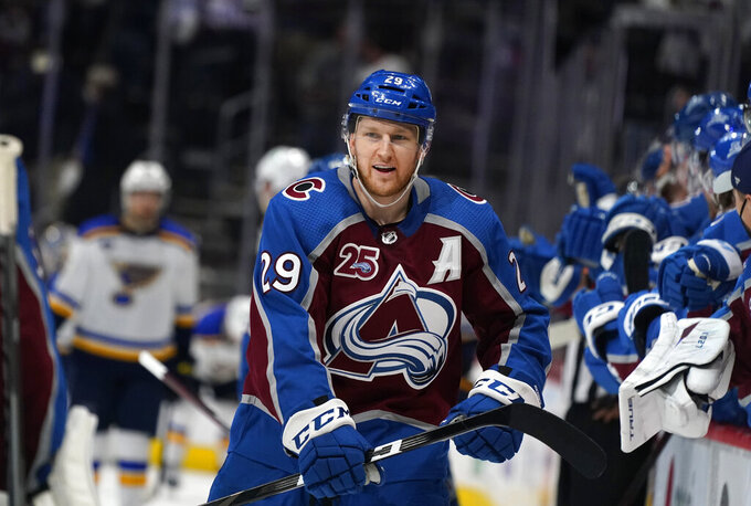 FILE - In this May 19, 2021, file photo, Colorado Avalanche center Nathan MacKinnon is congratulated at the bench after scoring his second goal of night in the third period of Game 2 of an NHL hockey Stanley Cup first-round playoff series against the St. Louis Blues, in Denver. The National Hockey League is ready to drop the puck on a full 82-game season with fans back in every arena and a wide-open race for the Stanley Cup. The best shot belongs to Colorado, the preseason Cup favorite, according to FanDuel Sportsbook and anyone who has watched Nathan MacKinnon try to will his team to a championship as one of the best players in the world. (AP Photo/David Zalubowski, File)