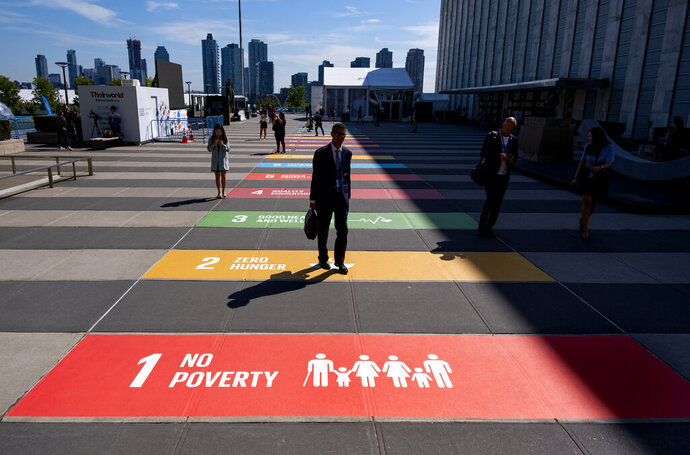 People walk along a plaza at United Nations Headquarters Saturday, Sept. 21, 2019. (AP Photo/Craig Ruttle)