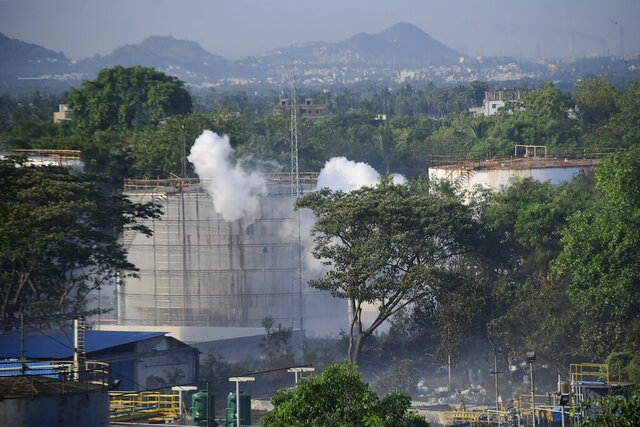 FILE - In this Thursday, May 7, 2020, file photo, smoke rises from LG Polymers plant, the site of a chemical gas leakage, in Vishakhapatnam, India. The plastics factory in India where a chemical gas leak killed 12 people and sickened hundreds more last week lacked federal environmental clearance but had been issued state permits to operate anyway, exposing a potentially dangerous enforcement gap in the country's laws. The owner of the LG Polymers plant in Andhra Pradesh state, South Korean chemicals giant LG Chem, said in a May 2019 affidavit that formed part of an application for the clearance that the company