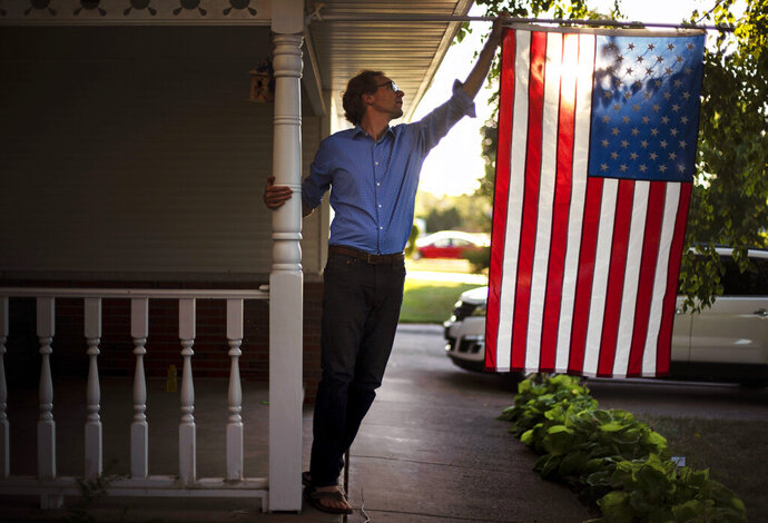 FILE - In this Aug. 18, 2020, file photo, Outagamie County Executive Tom Nelson adjusts the American flag hanging off his front porch in Appleton, Wis. Nelson officially launched his bid to unseat Republican Sen. Ron Johnson on Monday, Oct. 26, 2020. Johnson, currently midway through his second term, has not said yet whether he will seek a third term, run for governor or retire. (AP Photo/David Goldman, File)