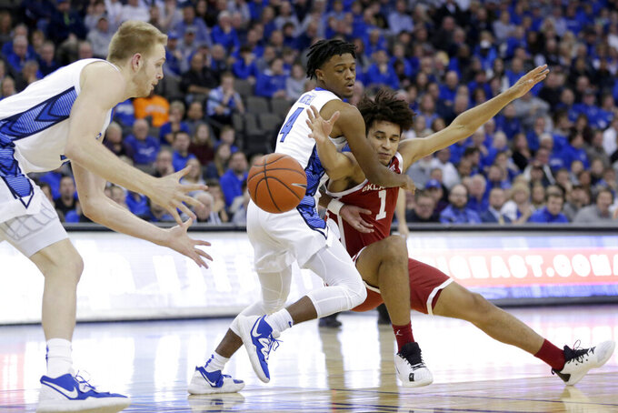 Oklahoma's Jalen Hill (1) loses the ball to Creighton's Kelvin Jones, left, while defended by Shereef Mitchell (4), during the first half of an NCAA college basketball game in Omaha, Neb., Tuesday, Dec. 17, 2019. (AP Photo/Nati Harnik)
