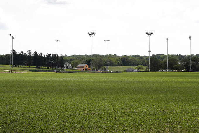 Light stands from a baseball field being built near the Field of Dreams movie site, rear, are seen, Friday, June 5, 2020, in Dyersville, Iowa. Major League Baseball is building the field a few hundred yards down a corn-lined path from the famous movie site in eastern Iowa but unlike the original, it's unclear whether teams will show up for a game this time as the league and its players struggle to agree on plans for a coronavirus-shortened season. (AP Photo/Charlie Neibergall)