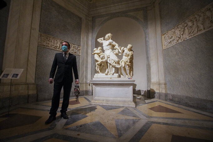 """Gianni Crea, the Vatican Museums chief """"Clavigero"""" key-keeper, walks past the Laocoon statue, a masterpiece of the sculptors of Rhodes dated around 40-30 B.C., on his way to open the museum's rooms and sections, at the Vatican, Monday, Feb. 1, 2021. Crea is the """"clavigero"""" of the Vatican Museums, the chief key-keeper whose job begins each morning at 5 a.m., opening the doors and turning on the lights through 7 kilometers of one of the world's greatest collections of art and antiquities. The Associated Press followed Crea on his rounds the first day the museum reopened to the public, joining him in the underground """"bunker"""" where the 2,797 keys to the Vatican treasures are kept in wall safes overnight. (AP Photo/Andrew Medichini)"""