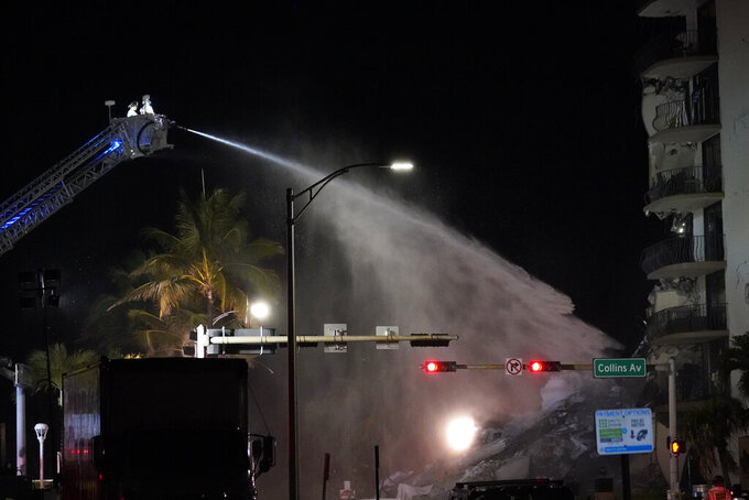 A Miami-Dade Fire Rescue team sprays water onto the rubble as rescue efforts continue where a wing of a 12-story beachfront condo building collapsed, late on Thursday, June 24, 2021, in the Surfside area of Miami.(AP Photo/Gerald Herbert)
