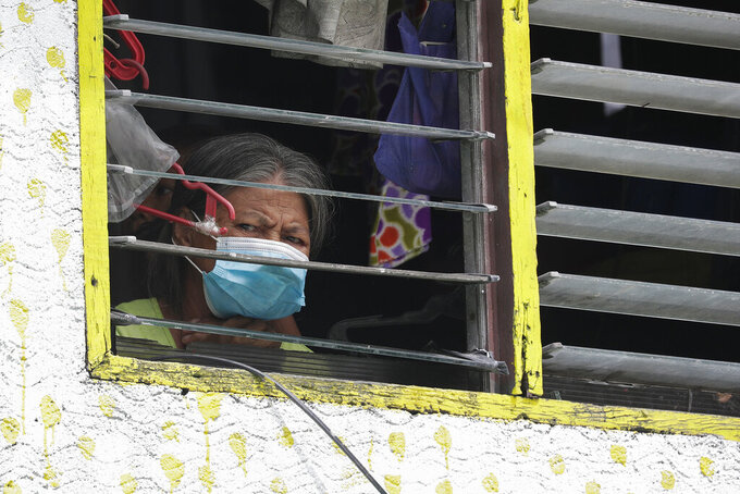 A woman resident wearing a mask looks out from her window as their area is placed under stricter lockdown measures to curb the spread of COVID-19 in Caloocan city, Philippines on Friday, Aug. 14, 2020. The capital and outlying provinces is still under lockdown due to rising COVID-19 cases. (AP Photo/Aaron Favila)