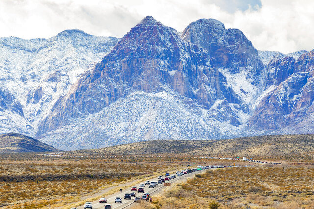 This photo by Yasmina Chavez of the Las Vegas Sun, of vehicles lined up to enter the snow-covered Red Rock Canyon following some cold and rainy weather on Dec. 27, 2019, won Photo of the Year honors from the Nevada Press Association Thursday, Sept. 24, 2020. (Yasmina Chavez/Las Vegas Sun via AP)