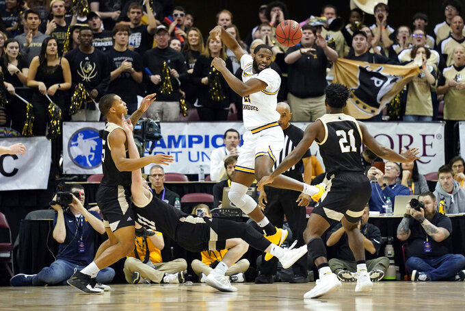 East Tennessee State forward Joe Hugley (21) leaps for the ball as Wofford forward Messiah Jones (25), Wofford guard Ryan Larson (11) and Wofford guard Tray Hollowell (21) scramble for it in the first half an NCAA men's college basketball championship game for the Southern Conference tournament, Monday, March 9, 2020, in Asheville, N.C. (AP Photo/Kathy Kmonicek)