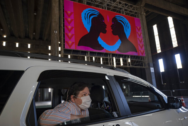 A woman takes in an art exhibit from the backseat of a car as she is driven through a warehouse displaying paintings and photos in Sao Paulo, Brazil, Friday, July 24, 2020, amid the new coronavirus pandemic. Galleries, cinemas, theaters and museums are closed due to the restrictive measures to avoid the spread of COVID-19, but a group of artists and a curator found a way to overcome the restrictions to share their art with the residents of Brazil's largest city. (AP Photo/Andre Penner)