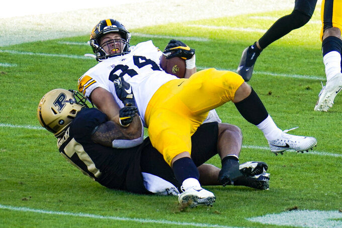 Iowa tight end Sam LaPorta (84) is tackled by Purdue linebacker Semisi Fakasiieiki (97) during the second quarter of an NCAA college football game in West Lafayette, Ind., Saturday, Oct. 24, 2020. (AP Photo/Michael Conroy)