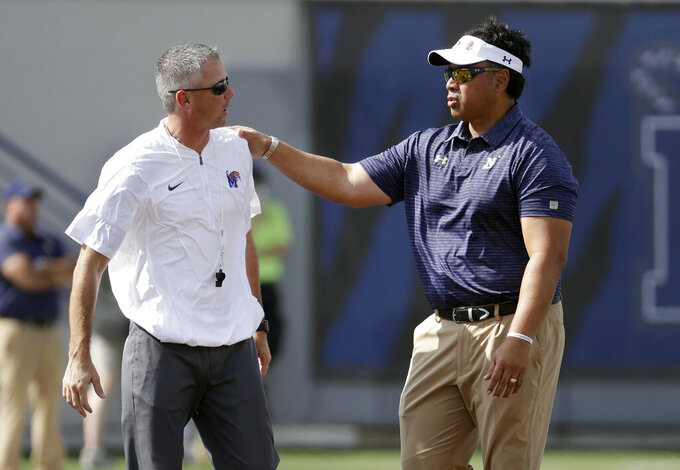 FILE - In this Oct. 14, 2017, file photo, Memphis head coach Mike Norvell, left, and Navy head coach Ken Niumatalolo talk before an NCAA college football game, in Memphis, Tenn. Three undefeated teams are left in the American Athletic Conference and two of them face each other Thursday, Sept. 26, 2019, to open this week's AAC slate.  Navy (2-0, 1-0 AAC) with its sometimes-baffling triple option offense visits Memphis for the ESPN-televised game, and only one will emerge to join SMU as the undefeated teams left in the conference. (AP Photo/Mark Humphrey, File)