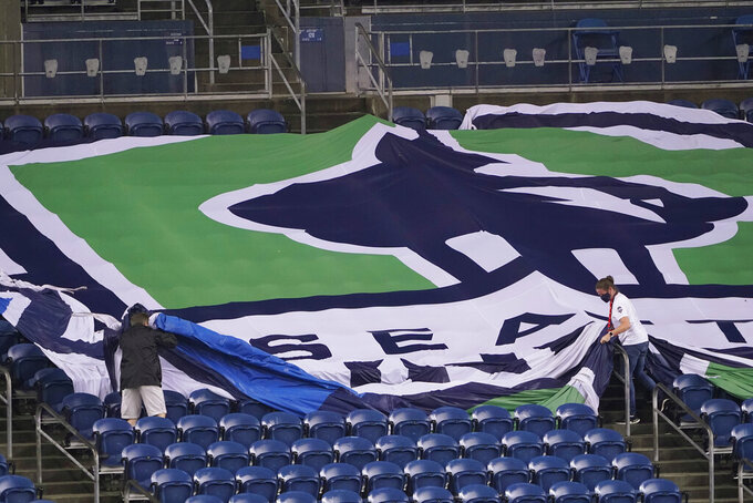 Workers remove a Seattle Sounders banner from the stands at CenturyLink Field following an MLS soccer match between the Sounders and Los Angeles FC, Friday, Sept. 18, 2020, in Seattle. The stadium is being prepared for Sunday's NFL football game between the Seattle Seahawks and the New England Patriots. (AP Photo/Ted S. Warren)