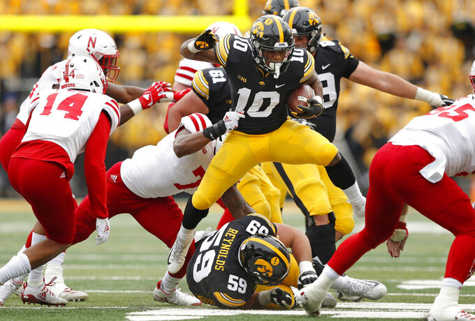 Iowa running back Mekhi Sargent (10) tries to break a tackle by Nebraska linebacker Mohamed Barry (7) during the first half of an NCAA college football game, Friday, Nov. 23, 2018, in Iowa City, Iowa. Iowa won 31-28. (AP Photo/Charlie Neibergall)