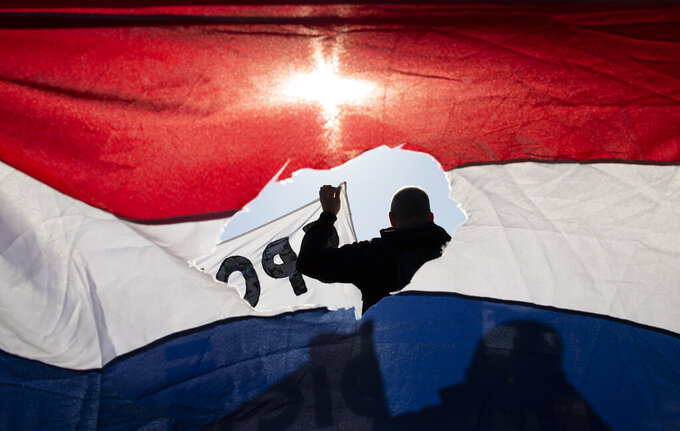 FILE - In this Sunday Feb. 28, 2012 file photo, demonstrators hold a Dutch flag with it's center cut out as another man, rear, holds a banner during a demonstration of several hundreds of people who protested against the coronavirus lockdown and curfew on Museum Square in Amsterdam, Netherlands. The Dutch vote next week in a general election. Many voters approve of Dutch Prime Minister Mark Rutte's handling of the crisis but his popularity has waned in recent weeks. (AP Photo/Peter Dejong, File)