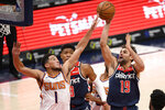 Washington Wizards guard Raul Neto (19) shoots against Phoenix Suns guard Devin Booker (1) during the second half of an NBA basketball game, Monday, Jan. 11, 2021, in Washington. (AP Photo/Nick Wass)