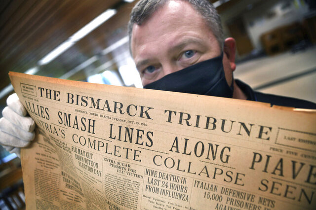 Shane Molander, state archivist at the North Dakota Heritage Center and State Museum in Bismarck, N.D., holds an original copy of The Bismarck Tribune dated Oct. 29, 1918, on Tuesday, July 28, 2020. Just below the national and international headlines is the local headline, center, Nine Deaths in Last 24 Hours From Influenza, reporting on the latest local death count for the Spanish flu epidemic that hit the state and country a century ago. Now, the State Historical Society of North Dakota is looking to collect personal stories of the coronavirus pandemic, The Bismarck Tribune reported. (Mike McCleary/The Bismarck Tribune via AP)