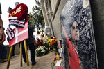 A cemetery worker places flowers at Michael Jackson's mausoleum at Forest Lawn Cemetery In Glendale, Calif. on Tuesday, June 25, 2019. Fans are gathering to pay tribute to the King of Pop on the 10th anniversary of his death.  (AP Photo/Richard Vogel)