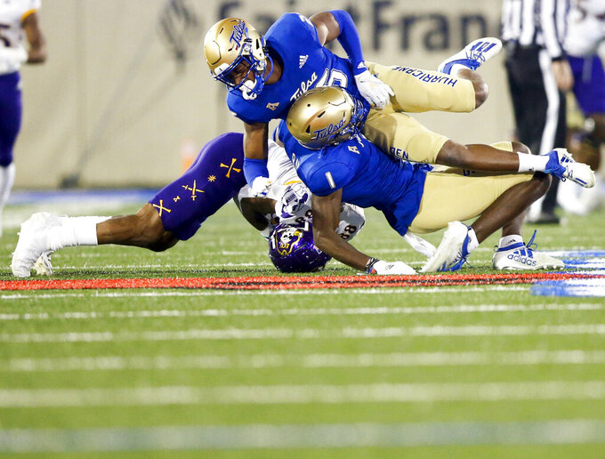 Tulsa safety Kendarin Ray (1) and cornerback Akayleb Evans (26) collide while tackling East Carolina wide receiver Jsi Hatfield (88) during an NCAA college football game Friday, Oct. 30, 2020, in Tulsa, Okla. (Ian Maule/Tulsa World via AP)
