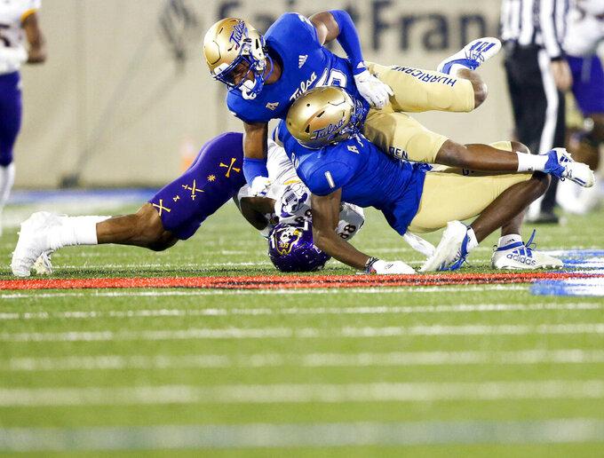 Tulsa safety Kendarin Ray (1) and cornerback Akayleb Evans (26) collide while tackling East Carolina wide receiver Jsi Hatfield (88) during an NCAA college football game Friday, Oct. 30, 2020, in Tulsa, Okla. (Ian Maule/Tulsa World via AP)