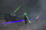 Anti-government demonstrators shine laser pointers a the police during a protest in Santiago, Chile, Tuesday, Nov. 12, 2019. Students in Chile began protesting nearly a month ago over a subway fare hike. The demonstrations have morphed into a massive protest movement demanding improvements in basic services and benefits, including pensions, health, and education. (AP Photo/Esteban Felix)