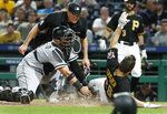 Pittsburgh Pirates' Adam Frazier (26) beats the tag by Chicago White Sox catcher Welington Castillo to score from first on a double by Gregory Polanco during the sixth inning of a baseball game in Pittsburgh, Tuesday, May 15, 2018. Watching the play is umpire Kewin Danley. (AP Photo/Gene J. Puskar)