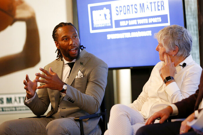 FILE - In this Thursday, July 18, 2019, file photo, NFL player Larry Fitzgerald, left, and Senior Director of Research and programs at The Women's Sports Foundation, Dr. Marjorie Snyder, serve as panelists at the DICK'S Sports Matter Panel Event in New York. Jon Gruden, Larry Fitzgerald and Alex Morgan have reached the summit of their professions. They all recognize the need for strong grass-roots sports programs, and they are doing something about it.  Working with DICK'S Sporting Goods Foundation, that trio announced a pledge to provide access to sports for one million youngsters over the next five years. DICK'S will match up to $1 million in donations made by customers to its foundation.  (Jason DeCrow/AP Images for DICK'S Sporting Goods, File)