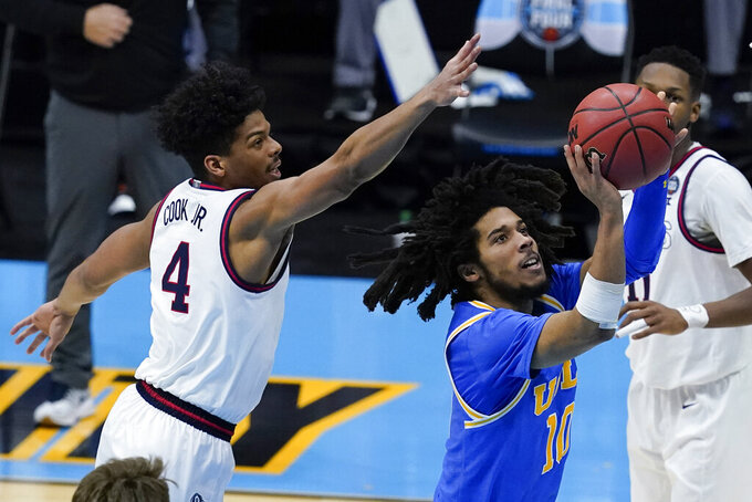 UCLA guard Tyger Campbell (10) shoots ahead of Gonzaga guard Aaron Cook (4) during the second half of a men's Final Four NCAA college basketball tournament semifinal game, Saturday, April 3, 2021, at Lucas Oil Stadium in Indianapolis. (AP Photo/Darron Cummings)
