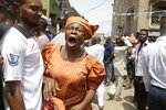 A woman cries as a body of child is recovered from the rubble of a collapsed building in Lagos, Nigeria, Wednesday March 13, 2019. Rescue efforts are underway in Nigeria after a three-storey school building collapsed while classes were in session, with some scores of children thought to be inside at the time. (AP Photo/Sunday Alamba)