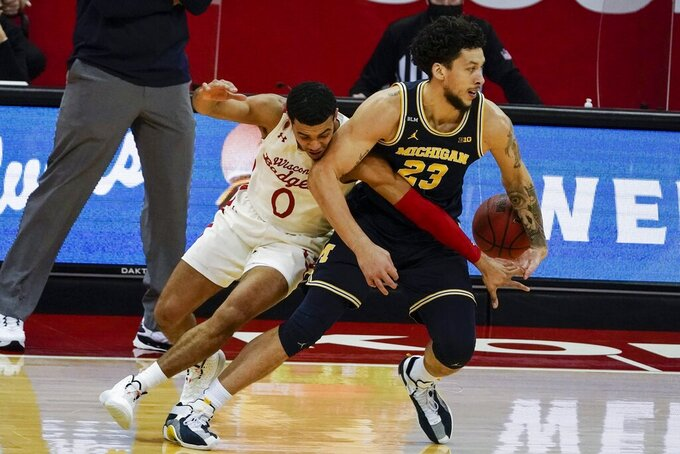 Wisconsin's D'Mitrik Trice tries to stop Michigan's Brandon Johns Jr. during the first half of an NCAA college basketball game Sunday, Feb. 14, 2021, in Madison, Wis. (AP Photo/Morry Gash)
