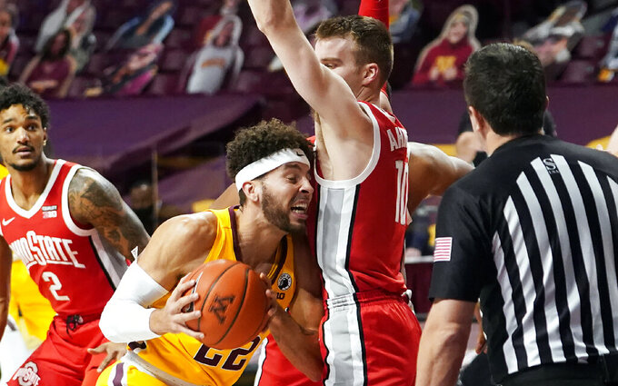 Minnesota's Gabe Kalscheur (22) drives into Ohio State's Justin Ahrens (10) in the first half of an NCAA college basketball game Sunday, Jan. 3, 2021, in Minneapolis. (AP Photo/Jim Mone)