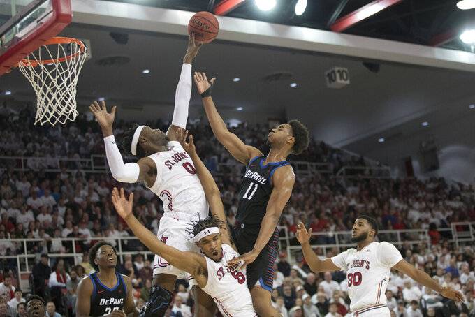 St. John's guard Justin Simon (5) and forward Sedee Keita (0) guard DePaul guard Eli Cain (11) in the first half of an NCAA college basketball game, Saturday, Jan. 12, 2019, in New York. (AP Photo/Mary Altaffer)