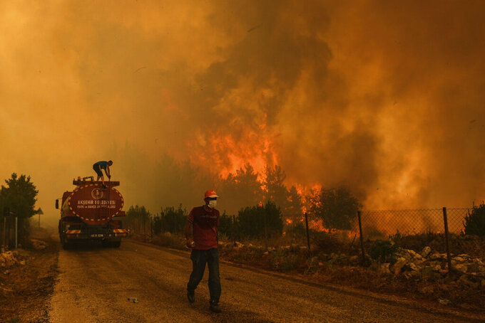 A man down a road in the fire-devastating Sirtkoy village, near Manavgat, Antalya, Turkey, Sunday, Aug. 1, 2021. More than 100 wildfires have been brought under control in Turkey, according to officials. The forestry minister tweeted that five fires are continuing in the tourist destinations of Antalya and Mugla. (AP Photo)