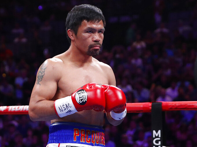 FILE - In this Saturday, July 20, 2019 file photo, Manny Pacquiao prepares to fight Keith Thurman in a welterweight title fight in Las Vegas. Qatar is preparing to host the 2022 World Cup and is now looking to attract big-name boxing. Promoter Bob Arum has been in talks with Qatari officials about bringing a welterweight unification bout between Manny Pacquiao and Terence Crawford to the energy-rich Gulf nation. (AP Photo/John Locher, File)