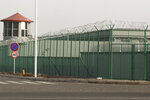 In this Monday, Dec. 3, 2018, file photo, a guard tower and barbed wire fences are seen around a facility in the Kunshan Industrial Park in Artux in western China's Xinjiang region. People in touch with state employees in China say the government in the far west region of Xinjiang is destroying documents and taking other steps to tighten control on information. (AP Photo/Ng Han Guan, File)