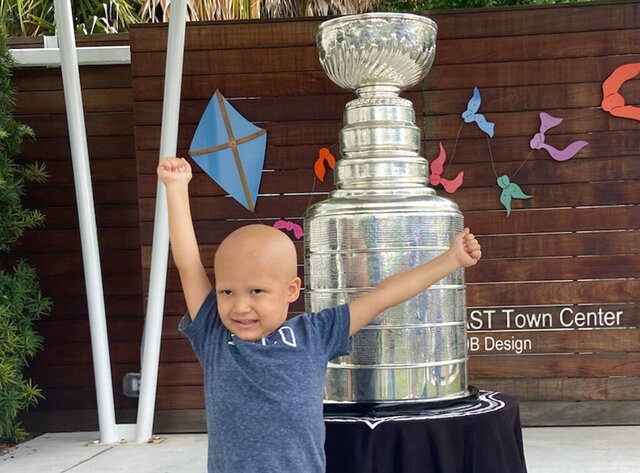 Kameron Bush, 3, poses with the Stanley Cup at the Children's Cancer Center in Tampa, Fla., on Oct. 16, 2020. The Tampa Bay Lightning took the Stanley Cup to the Children's Cancer Center as part of their local tour of stops after winning the National Hockey League's championship trophy Sept. 28 in Edmonton, Alberta. (Kristina Hjertkvist/Tampa Bay Lightning via AP)