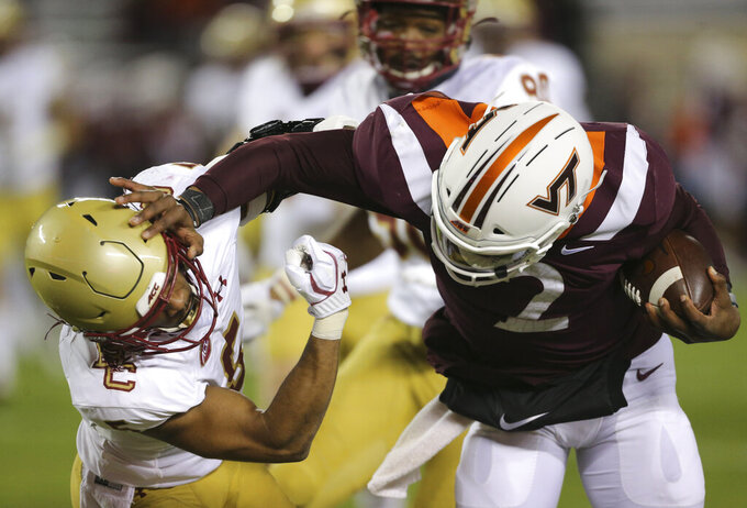Virginia Tech quarterback Hendon Hooker, right, stiff arms Deon Jones, left, of Boston College in the first half of an NCAA college football game in Blacksburg, Va. Saturday, Oct. 17, 2020. (Matt Gentry/The Roanoke Times via AP, Pool)