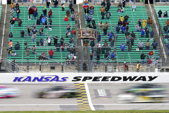 Fans watch as drivers take the green flag for a NASCAR Cup Series auto race at Kansas Speedway in Kansas City, Kan., Sunday, Oct. 18, 2020. (AP Photo/Orlin Wagner)