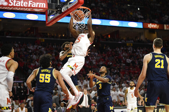 Maryland forward Jalen Smith (25) dunks against Michigan guard Eli Brooks (55), guard Zavier Simpson (3) and forward Isaiah Livers, back, during the second half of an NCAA college basketball game, Sunday, March 8, 2020, in College Park, Md. (AP Photo/Nick Wass)