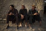 Afghans sit outside a mosque in a poor neighborhood where hundreds of internally displaced people from the eastern part of the country have been living for years, in Kabul, Afghanistan, Monday, Sept. 27, 2021. (AP Photo/Felipe Dana)