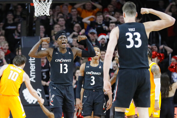 Cincinnati's Tre Scott (13) and Chris Vogt (33) react during the second half of an NCAA college basketball game against Tennessee, Wednesday, Dec. 18, 2019, in Cincinnati. (AP Photo/John Minchillo)