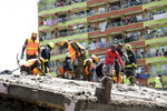 Rescue workers attend the scene of a collapsed building in in Tasia Embakasi, an east neighbourhood of Nairobi, Kenya on Friday Dec. 6, 2019.  A six-story building collapsed in Kenya's capital on Friday, officials said, with people feared to be trapped in the debris. Police say people have been rescued by residents using their bare hands. (AP Photo/Khalil Senosi)