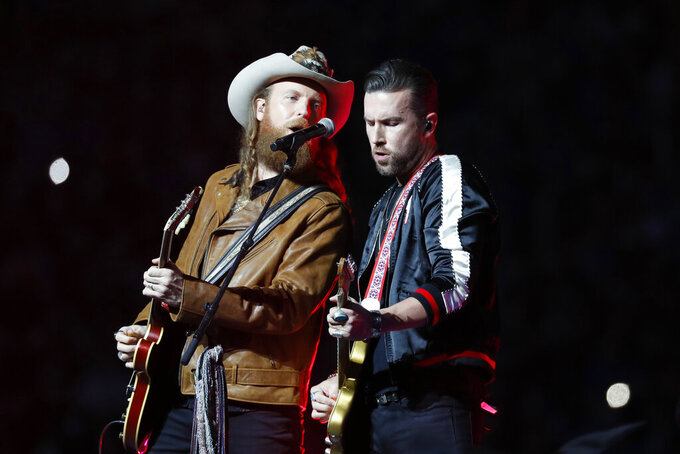 John Osborne, left, and T.J. Osborne of the Brothers Osborne musical duo perform during halftime of an NFL football game between the Detroit Lions and the Chicago Bears, Thursday, Nov. 28, 2019, in Detroit. (AP Photo/Paul Sancya)