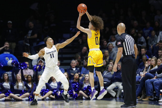 Lipscomb's KJ Johnson (0) shoots over Xavier's Bryce Moore (11) during the second half of an NCAA college basketball game, Saturday, Nov. 30, 2019, in Cincinnati. (AP Photo/John Minchillo)