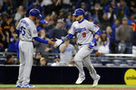 Los Angeles Dodgers' Yasmani Grandal is greeted by third base coach Chris Woodward (45) after hitting a grand slam during the ninth inning of a baseball game against the San Diego Padres, Monday, April 16, 2018, in San Diego. The Dodgers won 10-3. (AP Photo/Gregory Bull)
