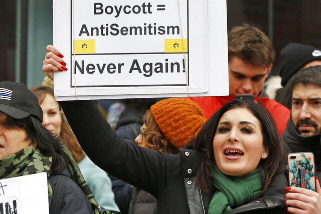 FILE - In this Jan. 19, 2019, file photo, political activist Laura Loomer holds uo a sign across the street from a rally organized by Women's March NYC after she barged onto the stage interrupting Women's March NYC director Agunda Okeyo who was speaking during a rally in New York. Loomer was escorted off the stage after the incident. A federal appeals court on Wednesday, May 27, 2020, upheld the dismissal of a lawsuit that accused Twitter, Facebook and other tech giants of conspiring to stifle the political views of a far-right activist and a conservative nonprofit.   A three-judge panel from the U.S. Court of Appeals for the District of Columbia Circuit ruled that Loomer and Freedom Watch Inc. don't have any viable claims that the companies violated their First Amendment free speech rights. (AP Photo/Kathy Willens, File)