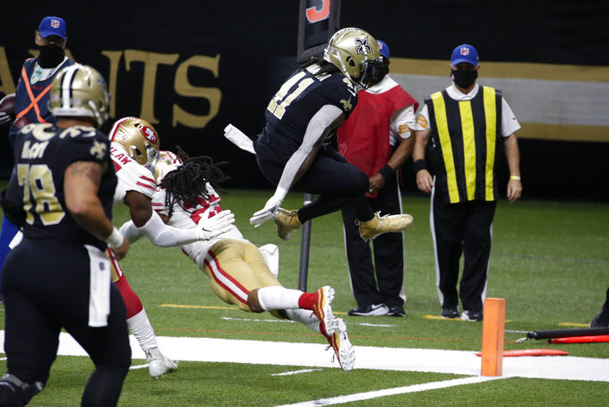 New Orleans Saints running back Alvin Kamara (41) leaps over San Francisco 49ers cornerback Ahkello Witherspoon (23) and into the end zone on a touchdown carry in the first half of an NFL football game in New Orleans, Sunday, Nov. 15, 2020. (AP Photo/Butch Dill)