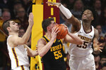 Iowa's Luka Garza (55) handles the ball against the defense of Minnesota's Alihan Demir, left, and Daniel Oturu, right, during an NCAA college basketball game Sunday, Feb. 16, 2020, in Minneapolis. (AP Photo/Stacy Bengs)