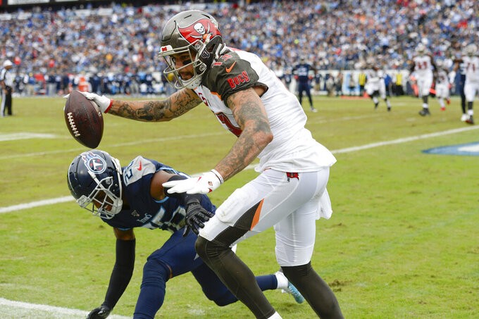 Tampa Bay Buccaneers wide receiver Mike Evans (13) scores a touchdown against Tennessee Titans cornerback Logan Ryan (26) on a 2-yard pass play in the second half of an NFL football game Sunday, Oct. 27, 2019, in Nashville, Tenn. (AP Photo/Mark Zaleski)